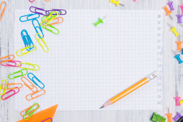 a sheet of paper in a cage, with a simple pencil for notes, surrounded by multicolored paper clips and buttons
