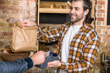 cropped view of smiling seller holding paper bag while customer paying for purchase with credit card