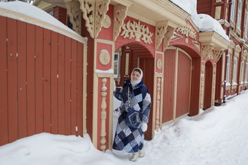 Russian girl and gate of wooden house in Tomsk city (Russia)