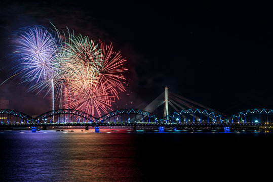 Colorful fireworks over river Daugava on Latvia's 100th birthday. Independence day celebration in Riga city with panoramic view over railway bridge.
