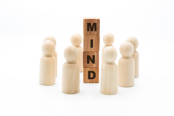 Wooden figures as business team in circle around word MIND