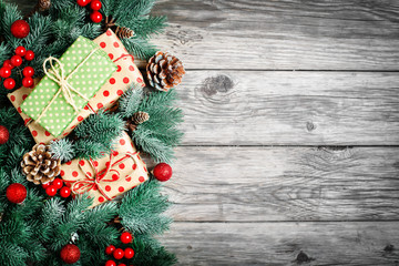 Merry Christmas and happy New year. Spruce branches and Christmas toys on a wooden background. Background with copy space. Top view. Christmas background.