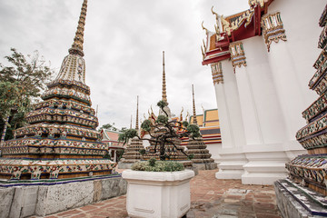 Panorama view of Ancient Stupas and pagoda in Wat Pho temple in Bangkok, Thailand. Famous landmark with contrasts thunder sky.