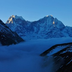Early morning in the Himalayas. Snow capped mountains Kangtega and Thamserku. Sea og fog, Gokyo Valley, Nepal.