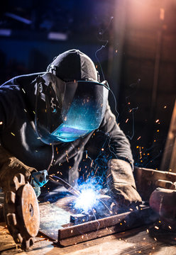 Welder working in workshop factory