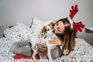 .Young and cheerful woman playing with her nice dog on Christmas morning, drinking a hot chocolate. Both with christmas costume. Lifestyle.