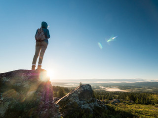 A traveler with a backpack on his back is standing on the top of a mountain, admiring the scenery and the sunrise