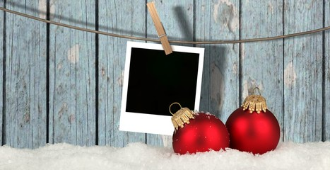 christmas background with instant photos - snow with christmas balls and blank instant photos hanging on the clothesline