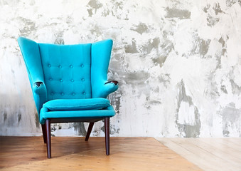 One blue armchair against a white and gray wall and floor