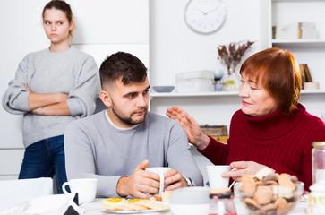Woman calming upset guy during quarrel with girlfriend