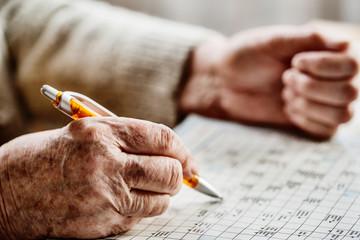 Seniorin löst ein Kreuzworträtsel im Seniorenheim