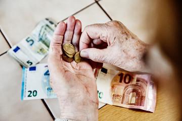 Hand einer Seniorin mit Bargeld, Seniorin zähl ihr Geld
