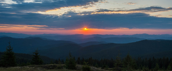 Majestic pink and purple sunrise in the morning in the mountains. Amazing sunrise over Carpathian mountains in the summer. Panoramic morning scene.