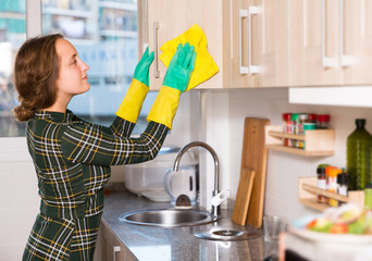 Woman cleaning kitchen surfaces