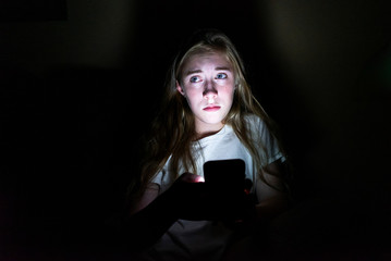 Upset girl sitting in the dark while using her smartphone. The light from the screen is illuminating her face.