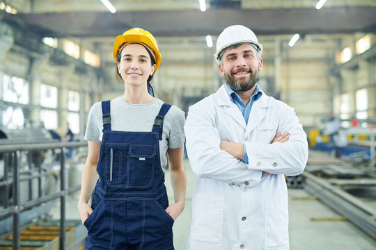 Waist up portrait of two smiling factory workers looking at camera while posing in industrial workshop