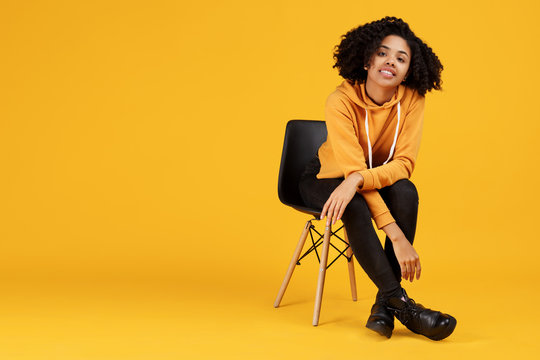 Portrait of charming african american young woman with beautiful smile dressed in casual clothes sitting on the stylish chair over yellow background.