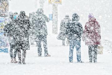 People on bus stop in snowfall