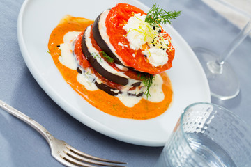 Tasty fried eggplants with tomatoes on white and spicy sauce  at  plate