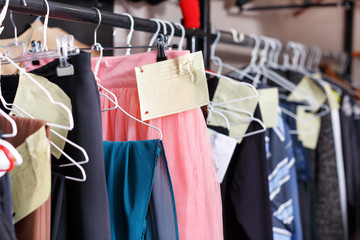 Clothes with tags on hangers in atelier