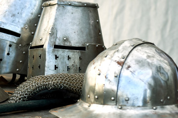 Steel medieval helmets with eyes slits on the table