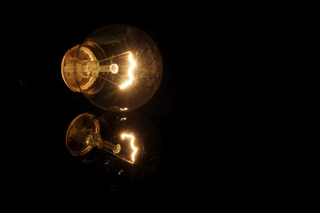 Glowing retro light bulb with reflection on black background