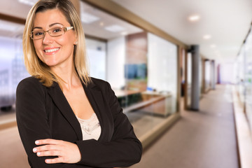 Brazilian business woman looking at camera in blurry office background. Copy space.