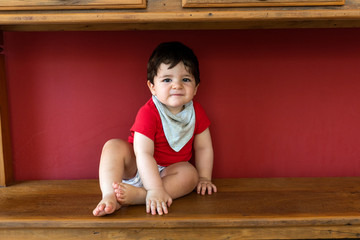Beautiful baby sitting under a wooden cupboard with red background