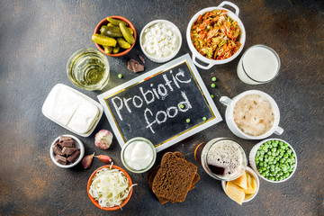 Super Healthy Probiotic Fermented Food Sources, drinks, ingredients, on dark concrete background copy space top view