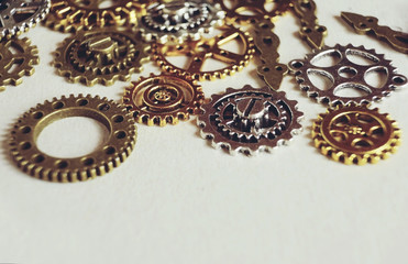 A steampunk and ancient macro about machinery made of bronze, silver and gold gears with beige background