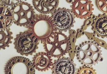 A steampunk and ancient flat macro about machinery made of bronze, silver and gold gears with beige background