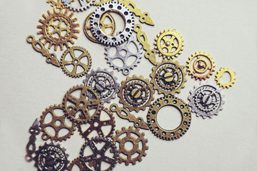 A steampunk and ancient flat macro about machinery made of bronze, silver and gold gears like heart shaped with beige background