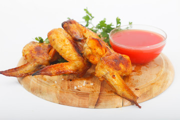 Grilled chicken wings with ketchup and spices  on a wooden board. Traditional food buffalo, white background.