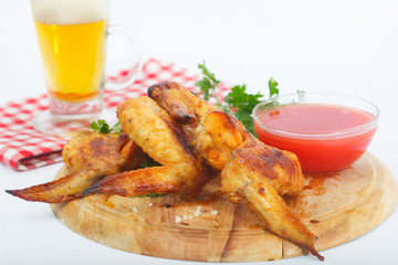 Bbq chicken wings with red sauce and beer. Grilled chicken wings with glass of beer..
