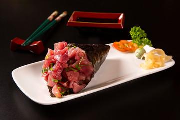 Tuna fish temaki sushi into a white plate in black background