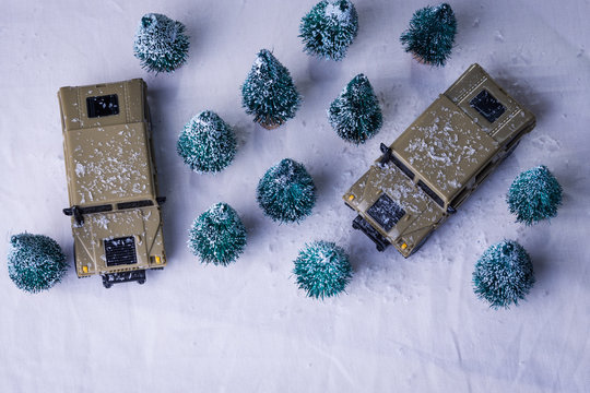 Toy military vehicles amid tory evergreen trees in winter