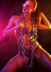 Sporty fit woman dancer and athlete with chains makes fitness exercising on black background with colorful lights.