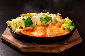 delicious Teppanyaki Salmon food with chopsticks and vegetable in the iron pan.