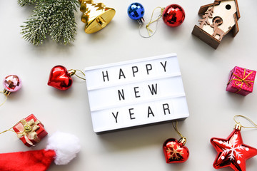 HAPPY NEW YEAR text on lightbox composition and of Christmas decorations on white table background copy space,Business Concept.