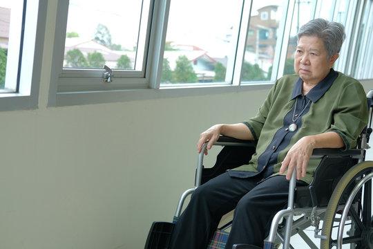 bored depressed elder woman in wheelchair. elderly female feeling sad lonely