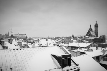 Krakow in Christmas time, aerial view on snowy roofs in central part of city. St. Mary's Basilica on Main Square. BW photo. Poland. Europe.