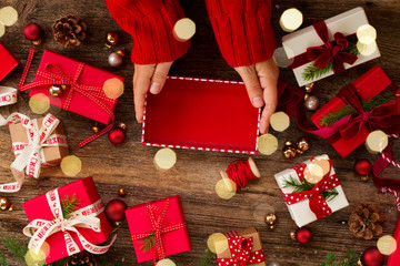 Christmas gift giving - hands preparing and wrapping red and white paper christmas gift boxes on wooden background with bokeh lights