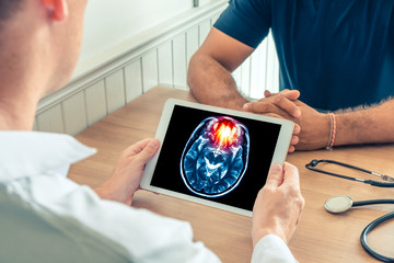 Doctor holding a digital tablet with x-ray of brain of the patient. Brain cancer or headache prevention