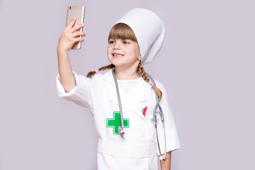 Smiling girl in medical uniform holding smartphone and take selfie