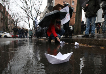A demonstrator launches a paper boat during a rally to support the Ukrainian navy in front of the Russia Consulate in Kharkiv