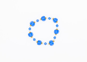 blue colored and variously sized beads bracelet on white background