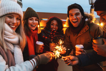 Young friends talking with each other drinking coffee outdoors winter concept holding bengal lights.