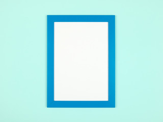 Flat lay pastel colored background with empty picture frame