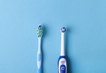 electric and classic toothbrush on a blue background