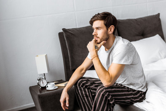 thoughtful young man in pajamas sitting on bed and looking away in the morning